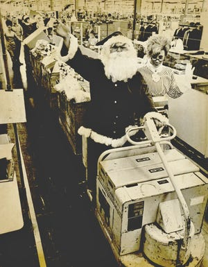 Santa Claus guides a sleigh of gondola carts through Oklahoma City's Western Electric plant on Dec. 21, 1970. Santa and Mrs. Claus were taking the annual trip through the plant, collecting thousands of toy donations from Western Electric's employees. A second Santa and helper followed the train of carts to help with the collection of Christmas gifts for area children. [BOB ALBRIGHT/THE OKLAHOMAN ARCHIVES]