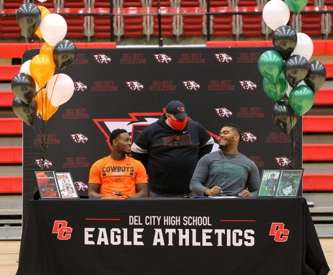 Del City football coach Mike Dunn with Donovan Stephens signing with Oklahoma State and Kevin Greene signing with North Texas on Thursday. [Doug Hoke/The Oklahoman]