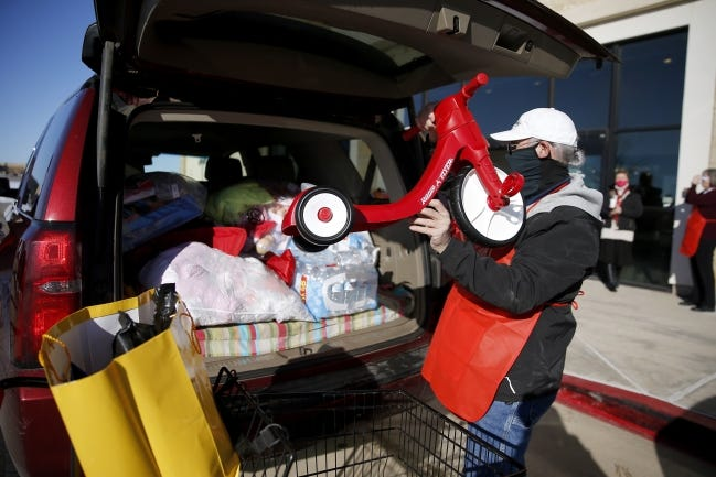 Volunteer Chip DesCombes loads gifts for a family into a vehicle during distribution for The Salvation Army of Central Oklahoma's 2020 Angel Tree program in Oklahoma City. [Bryan Terry/The Oklahoman]