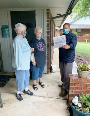 """The Rev. Chris Finley, right, Baptist Village Communities' director of chaplain services, sings hymns with two residents at one of the Baptist Village residential centers during what he described as a """"porch visit."""" [Jason Davis/Baptist Village Communities]"""