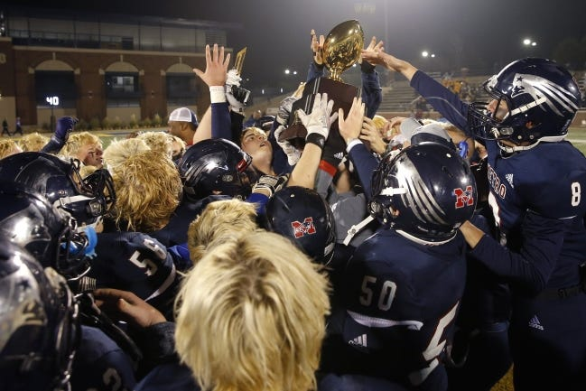 Tulsa Metro Christian celebrates with the trophy after winning last season's Class 2A football state championship against Vian at Wantland Stadium in Edmond. [Bryan Terry/The Oklahoman]