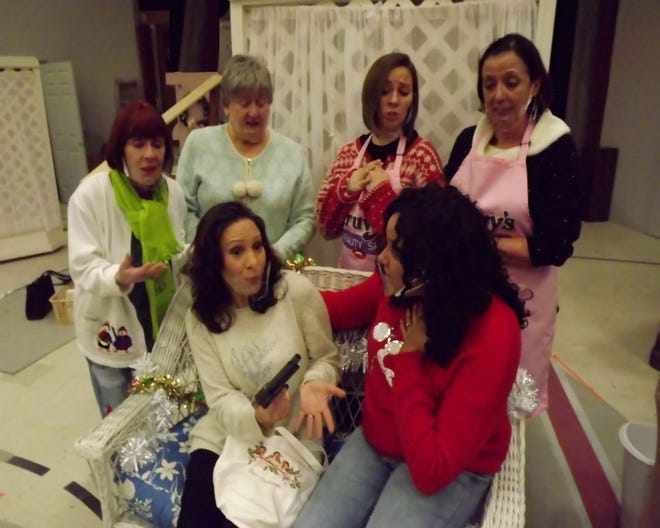 """M'Lynn (Katy Hayes) shows the gun she's confiscated from her husband to her daughter Shelby (Kat Adams), Ouiser (Lana Henson), Clariee (Chris Harris), Annelle (Caitlin Cairns), and beauty shop owner Truvy (Lilli Bassett) in Jewel Box Theater's production of """"Steel Magnolias."""" [Photo provided]"""
