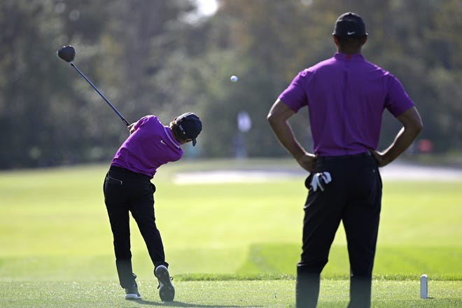 Tiger Woods, right, watches as his son Charlie tees off on the second hole during the first round of the PNC Championship golf tournament. [AP Photo/Phelan M. Ebenhack]