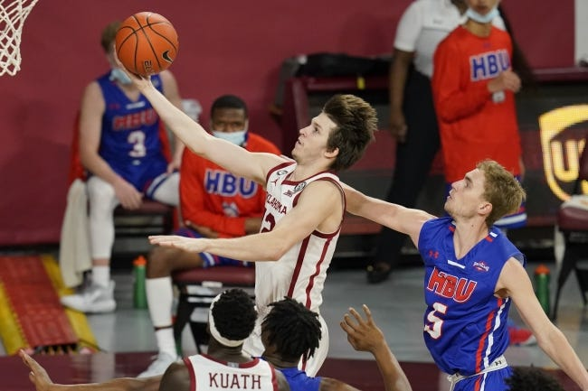 OU guard Austin Reaves goes to the basket in front of Houston Baptist guard Hunter Janacek, right, in the first half Saturday. [AP Photo/Sue Ogrocki]