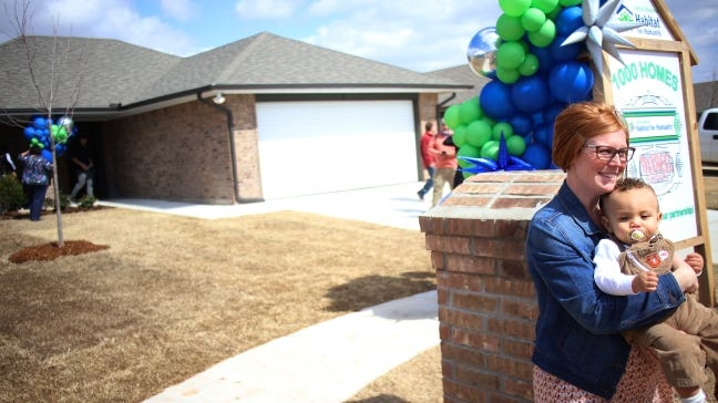 Brittani Githiri holds her son, Piaget, on March 9 by the mailbox of her new home, Central Oklahoma Habitat for Humanity's 1,000th home. [DOUG HOKE/THE OKLAHOMAN ARCHIVES]