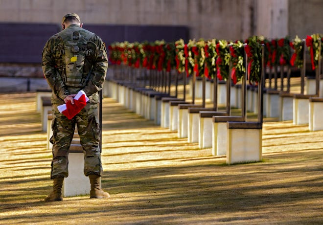 """A soldier from Fort Sill stands over a memorial chair while on a tour of the Oklahoma City National Memorial & Museum during the """"Soldiers´ Day Out"""" troop movement in Oklahoma City on Monday. The annual Oklahoma City tour and day on the town is held for military personnel not heading home for Christmas holiday. [Photos by Chris Landsberger/The Oklahoman]"""
