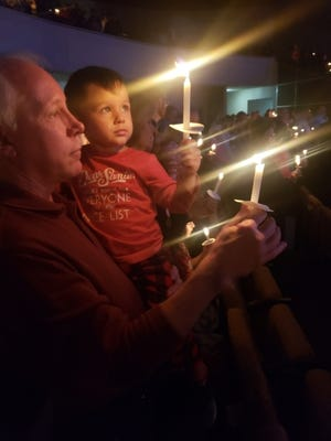 Max Lonsdale holds Ryker Perales as they both hold lighted candles during a Candlelight Service held on Christmas Eve in a previous year at Council Road Baptist Church in Bethany. [Photo provided]