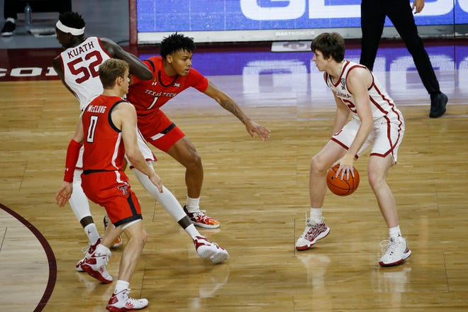 Oklahoma's Austin Reeves (12) watches as Kur Kuath (52) moves between Texas Tech's Mac McClung (0) and Terrence Shannon Jr. (1) during the first half of an NCAA college basketball game in Norman, Okla., Tuesday, Dec. 22, 2020. (AP Photo/Garett Fisbeck)