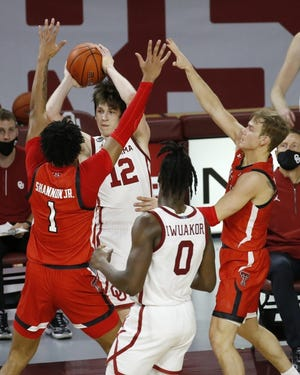 Oklahoma's Austin Reaves, middle, looks to pass the ball as Texas Tech's Terrence Shannon Jr., left, and Mac McClung, right, defend on Tuesday. Texas Tech won 69-67. [AP Photo/Garett Fisbeck]