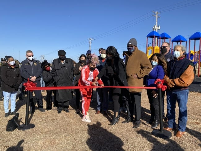 Gina Darby and Angela Scobey cut the ribbon during a ribbon-cutting ceremony for a new basketball court and playground on the property of Ebenezer Baptist Church in northeast Oklahoma City. [Carla Hinton/The Oklahoman]