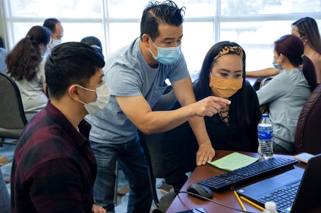 Problems still linger despite the Oklahoma Employment Security Commission's efforts to address them. Here, translator Calvin Nguyen, center, helps a client with the unemployment filing process in July during an unemployment filing event in Midwest City. [Chris Landsberger/The Oklahoman]