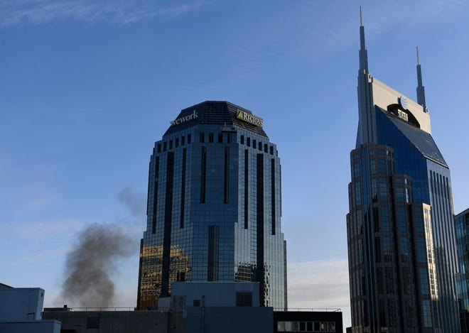 Plumes of smoke rise next to the Regions Building near the explosion reported in the area on Friday, Dec. 25, 2020 in Nashville, Tenn. Buildings shook in the immediate area and beyond after a loud boom was heard early Christmas morning. (Andrew Nelles/The Tennessean via AP)