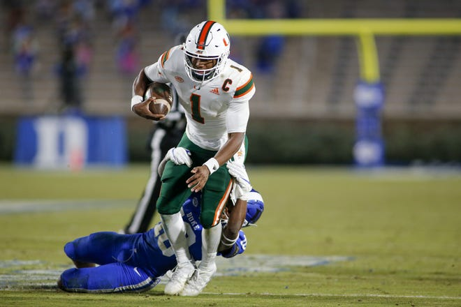 Miami quarterback D'Eriq King (1) fights for yards in a 48-0 win at Duke on Dec. 5. [Nell Redmond/USA TODAY Sports]