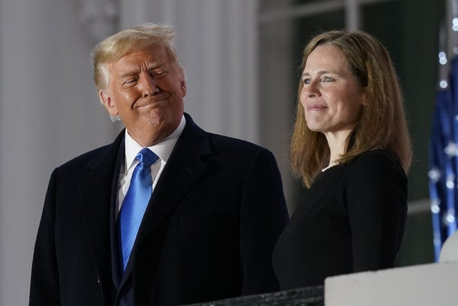 President Donald Trump and Amy Coney Barrett stand on the Blue Room Balcony after Supreme Court Justice Clarence Thomas administered the Constitutional Oath to her on the South Lawn of the White House in October. [AP Photo/Patrick Semansky]