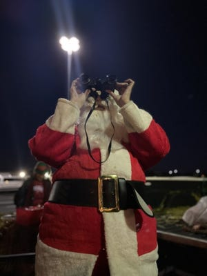 Dressed in a Santa Claus costume, Nancy Miller of Edmond uses a binoculars to see the alignment of Jupiter and Saturn. [Carla Hinton/The Oklahoman]