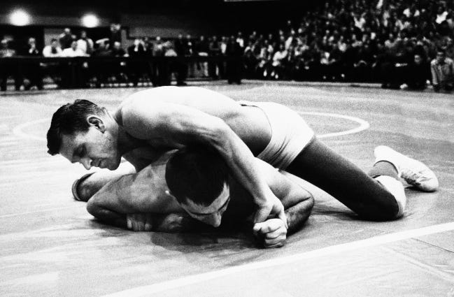 OU's Danny Hodge maneuvers Iowa's Tom Shaheen into the fall with a bar-arm and headlock during a match on March 8, 1957, in Norman. [AP Photo/File]