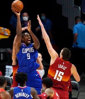 Los Angeles Clippers forward Serge Ibaka shoots over Denver Nuggets center Nikola Jokic during the first half of an NBA basketball game Friday, Dec. 25, 2020, in Denver. (AP Photo/David Zalubowski)