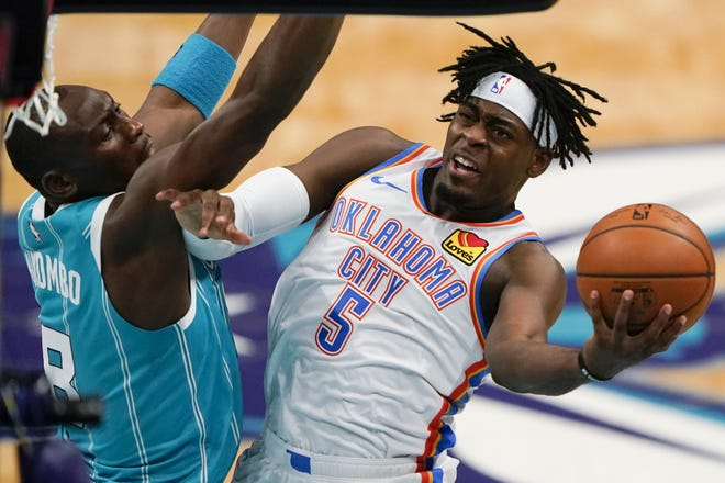 Thunder guard Luguentz Dort shoots around Hornets center Bismack Biyombo during the first half of a 109-107 win Saturday in Charlotte, N.C. [AP Photo/Chris Carlson]