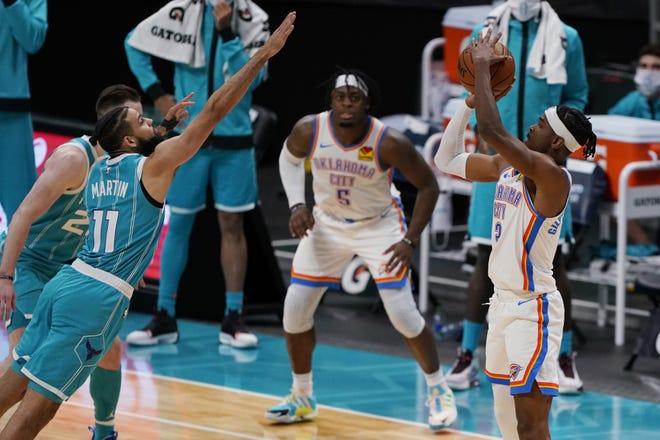 Thunder guard Shai Gilgeous-Alexander, right, shoots the go-ahead basket over Hornets forward Cody Martin during a 109-107 win Saturday in Charlotte, N.C. [AP Photo/Chris Carlson]