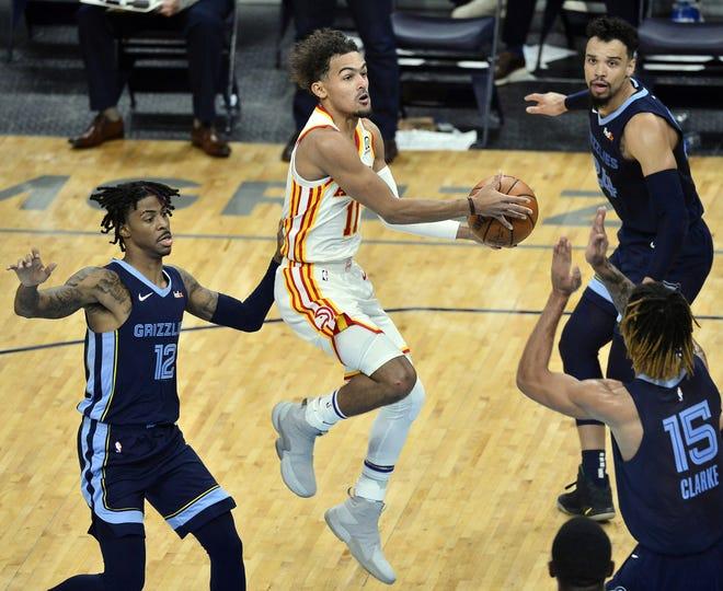 Atlanta Hawks guard Trae Young (11) looks to shoot between Memphis Grizzlies guard Ja Morant (12), forward Brandon Clarke (15), and guard Dillon Brooks. [AP Photo/Brandon Dill]