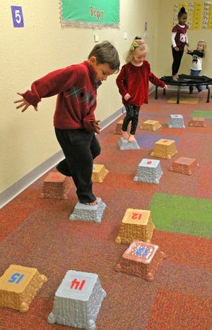 """Zanden Fullbright and Hannah Garner learn to count by playing on the stepping stones in the """"body shop"""" at the Shawnee Early Childhood Center. [PHOTO PROVIDED]"""