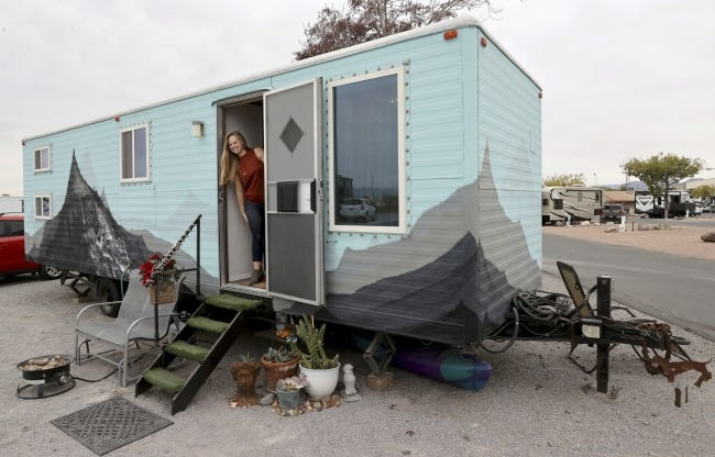 Hannah Doss poses for a photo Dec. 11 at her tiny home in Boulder City, Nev. Doss bought the old railroad trailer that she and her parents converted into a tiny house. [K.M. Cannon/Las Vegas Review-Journal/via AP]