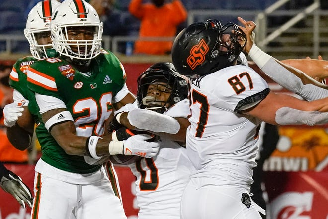Oklahoma State running back LD Brown, center, scores a touchdown as he gets past Miami safety Gurvan Hall Jr. (26) and gets a block from teammate tight end Logan Carter (87) during the first half of the Cheez-it Bowl NCAA college football game, Tuesday, Dec. 29, 2020, in Orlando, Fla. (AP Photo/John Raoux)