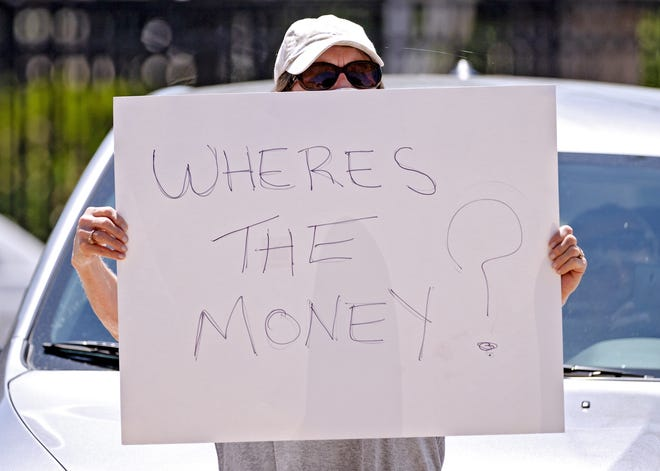 The U.S. Department of Labor said Tuesday that two unemployment programs that expired Saturday will pay out benefits without a gap in the number of eligible weeks, despite questions about whether the timing of their renewal would delay benefits. In this file photo, a woman protests in May over previous unemployment delays. [THE OKLAHOMAN ARCHIVES]
