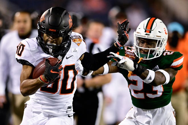 Oklahoma State wide receiver Brennan Presley (80) makes a reception as Miami Hurricanes cornerback Te'Cory Couch (23) defends during the first half of the Cheez-It Bowl at Camping World Stadium in Orlando, Fla. [Douglas DeFelice/USA Today Sports]