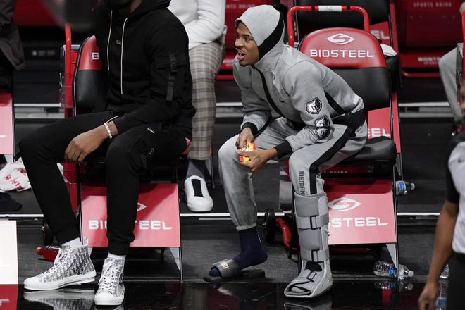 Memphis Grizzlies guard Ja Morant, right, wears a boot on his left foot after suffering an injury during the team's game against the Brooklyn Nets on Monday. [AP Photo/Kathy Willens]