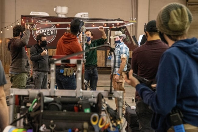 Grip specialist Jon Shyock, center with cowboy hat, works with students on scene set-up at Prairie Surf Studio in downtown Oklahoma City. The food truck and string lighting is a set that will be shot as a nighttime scene. [PROVIDED]