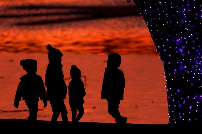 Children are silhouetted against a pond as they look at Christmas lights at a park in Lenexa, Kan. [Charlie Riedel/Associated Press]