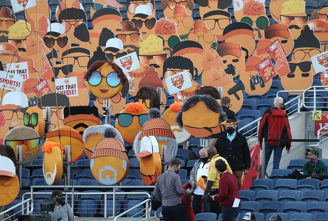Fans walk in front of Cheez-It fan head icons placed in seats before the start of Oklahoma State's 37-34 win over Miami on Tuesday at Camping World Stadium in Orlando, Fla. [Stephen M. Dowell/Orlando Sentinel]