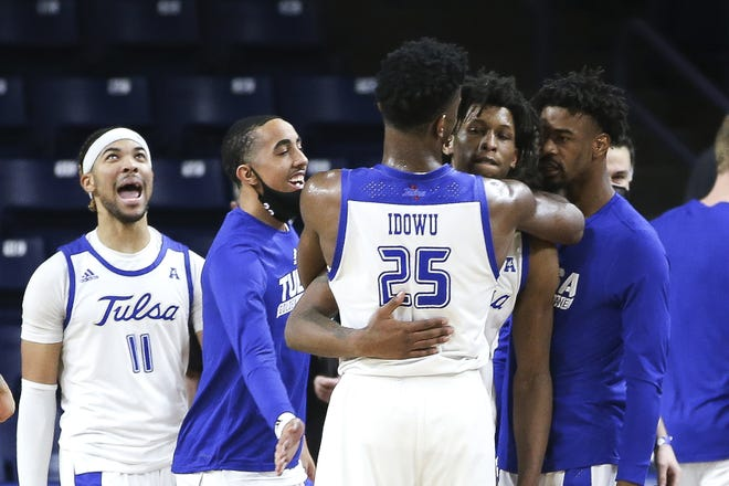Tulsa's Brandon Rachal is hugged by Rey Idowu (25) after Rachal made two free throws during the final second of a 65-64 win against fifth-ranked Houston on Tuesday. [AP Photo/Dave Crenshaw]