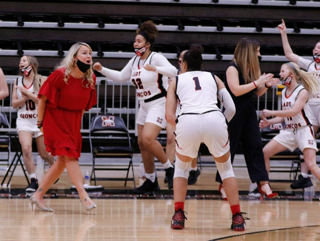 MHS coach Katie Bass and team celebrate their double overtime win during the high school girls basketball game between Edmond North and Mustang at the Cornerstone Bank Mustang Holiday Classic played at Mustang High School Event Center, Wednesday, December 30, 2020. [Doug Hoke/The Oklahoman]
