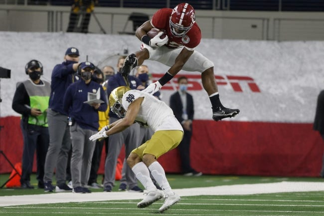 Alabama running back Najee Harris (22) hurdles Notre Dame cornerback Nick McCloud (4) as he carries the ball for a long gain in the first half of the Rose Bowl on Friday in Arlington, Texas. [AP Photo/Michael Ainsworth]