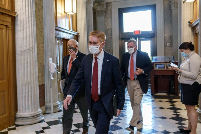 From left, Sen. Roger Wicker, R-Miss., Sen. James Lankford, R-Okla., and Sen. Richard Burr, R-N.C., arrive for votes during a rare weekend session to advance the confirmation of Judge Amy Coney Barrett to the Supreme Court, at the Capitol in Washington, Sunday, Oct. 25, 2020. (AP Photo/J. Scott Applewhite)