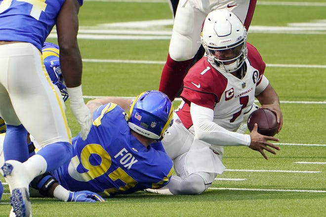 Cardinals quarterback Kyler Murray is sacked by Los Angeles Rams defensive end Morgan Fox (97) during the first half. Murray exited the contest with an ankle injury. [AP Photo/Jae C. Hong]
