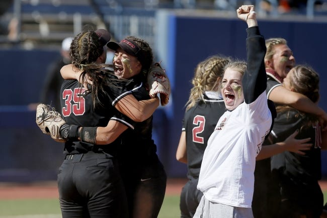 Tuttle's Hannah Morales, center, hugs Rylan Dooner, left, as they celebrate winning the Class 4A state softball championship on Oct. 17. [Bryan Terry/The Oklahoman]