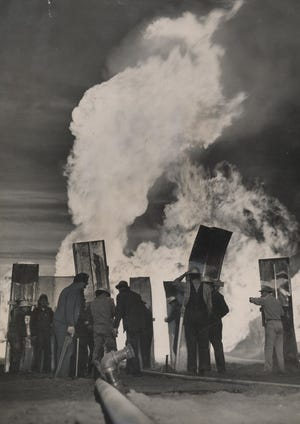Oil field firefighters and workers stand near a burning well south of Elk City in January 1950. The men carried shields of metal to protect themselves from heat and debris coming from the Shell Oil Co. No. 1 Reynolds-Hubbard well. Firefighters had been brought in from Houston to try to gain control of the well inferno. After burning for days, gas pressure began to fall as mud, soil and rock within the well finally blocked the gas and oil flow, extinguishing the fire. This photo was published on the cover of The Daily Oklahoman's Sunday Magazine. [A.Y. OWEN/THE OKLAHOMAN ARCHIVES]