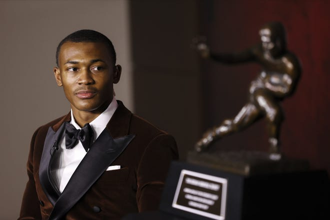 Alabama receiver DeVonta Smith looks at the Heisman Trophy after being named the winner on Tuesday in Tuscaloosa, Ala. Smith finished with 447 first-place votes and 1,856 points to easily outdistance Clemson's Trevor Lawrence (222, 1,187), Alabama teammate Mac Jones (138, 1,130) and Florida's Kyle Trask (61, 737). [Kent Gidney/Heisman Trophy Trust via AP]