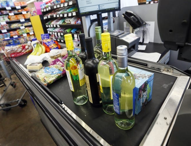 Wine and beer sits on the conveyor belt at a checkout lane next to groceries inside the Homeland grocery store at Classen and NW 18 on the first day of wine and strong beer sales in grocery stores. THE [OKLAHOMAN ARCHIVES]