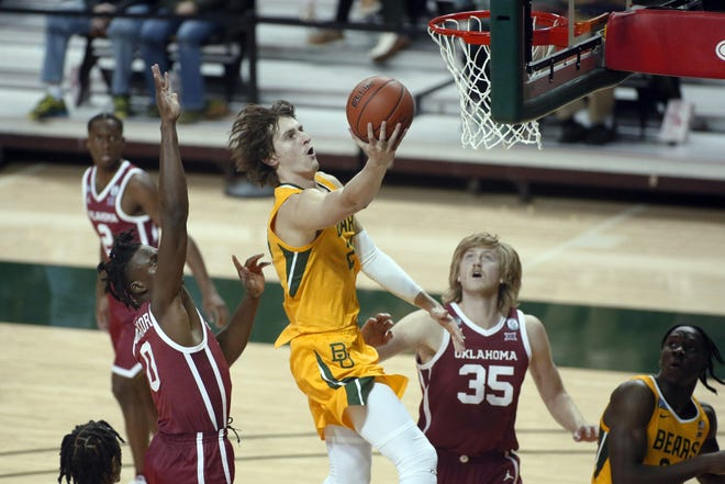 Baylor guard Matthew Mayer, center, goes to the basket on OU forwards Victor Iwuakor, left and Brady Manek, right, during the second half Wednesday. [AP Photo/Ray Carlin]