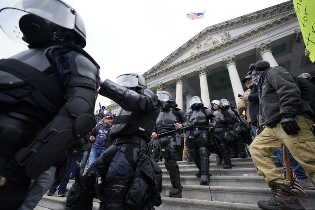 Police in riot gear walk out of the U.S. Capitol, Wednesday, Jan. 6, 2021. (AP Photo/Manuel Balce Ceneta)