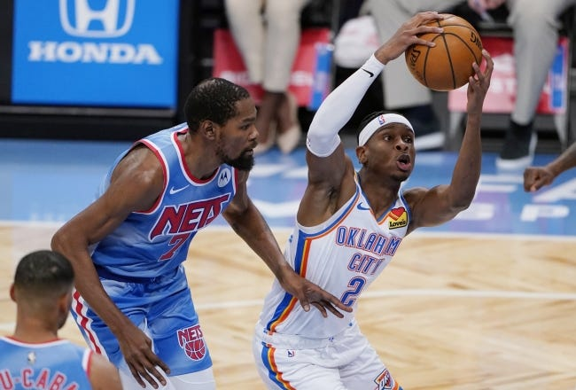 Thunder guard Shai Gilgeous-Alexander (2) drives past Nets forward Kevin Durant in the first quarter of OKC's win Sunday in New York. [AP Photo/Kathy Willens]