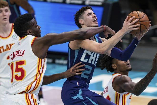 Atlanta Hawks center Clint Capela (15) fouls Charlotte Hornets guard LaMelo Ball (2) during the second half Saturday in Charlotte, N.C. [AP Photo/Jacob Kupferman]