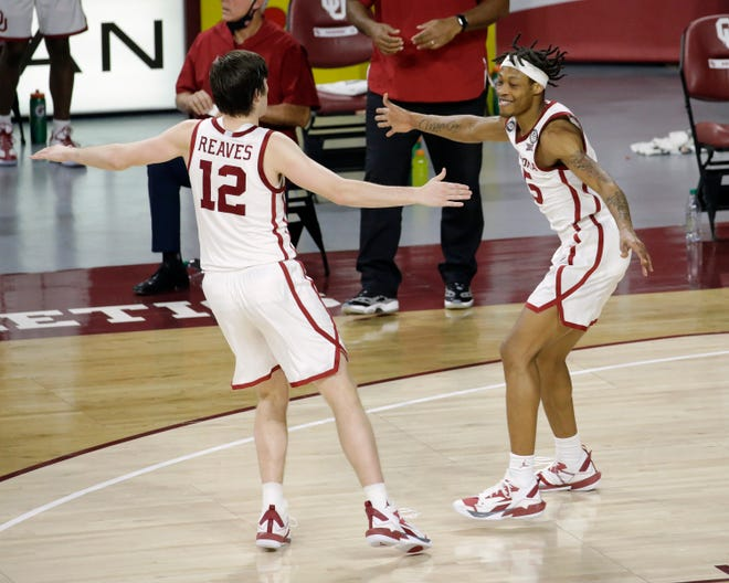 Oklahoma's Alondes Williams (15) celebrates with Austin Reaves (12) during the second half of the team's NCAA college basketball game against TCU in Norman, Okla., Tuesday, Jan. 12, 2021. (AP Photo/Garett Fisbeck)