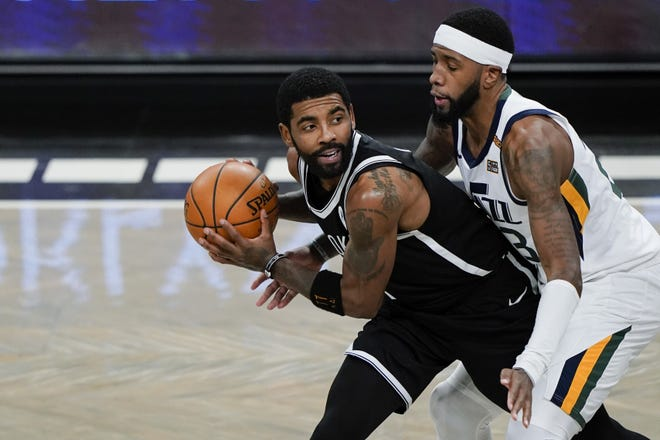 Utah's Royce O'Neale (right) defends Brooklyn's Kyrie Irving during a game on Jan. 5 in New York. [AP Photo/Frank Franklin II]