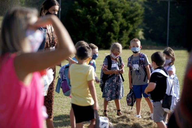 Students wait outside Charles Haskell Elementary on their first day of school in Edmond Public Schools on Aug. 20. [Bryan Terry/The Oklahoman]