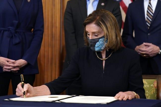 House Speaker Nancy Pelosi signs the article of impeachment against President Donald Trump on Wednesday, Jan. 13, 2021. [AP Photo/Alex Brandon]